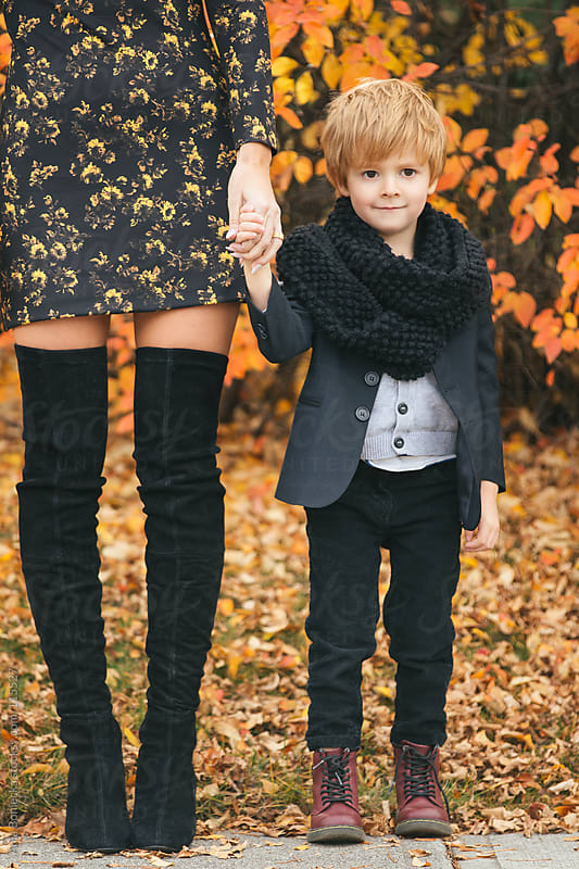 A young boy standing by his mother's side holding her hand, softly smiling by Ania Boniecka for Stocksy United