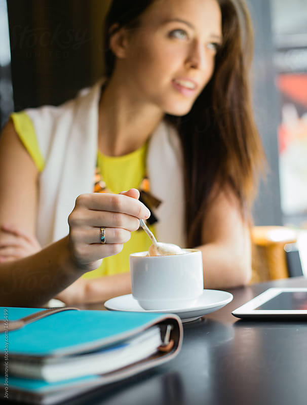 Business woman sitting in coffee shop and drinking coffee by Jovo Jovanovic for Stocksy United