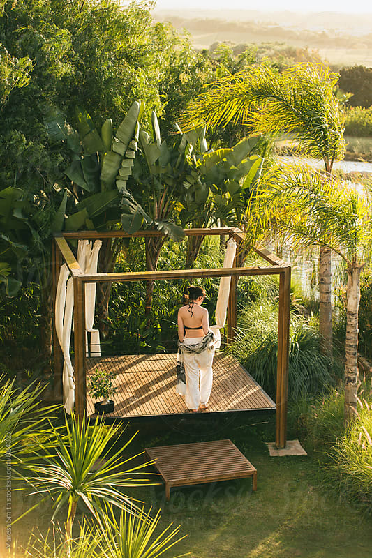 A brunette holiday maker walking on a picturesque patio surrounded by tropical plants by Maresa Smith for Stocksy United