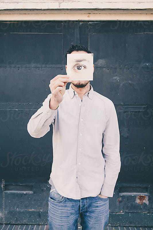 Young man holding a picture in front of his face with his eye on it by Ivo de Bruijn for Stocksy United