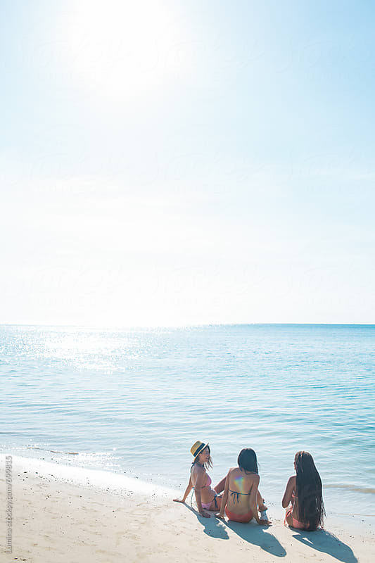 Three Young Women Sitting at the Beach by Lumina for Stocksy United