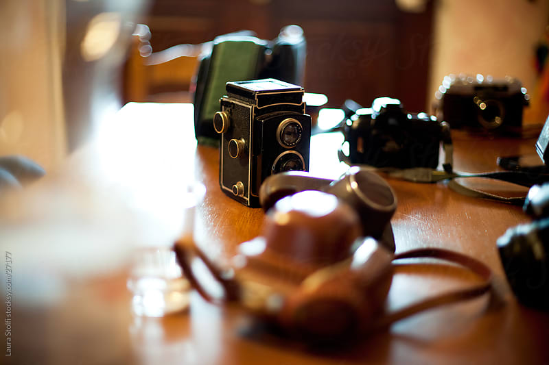 Vintage cameras collection on wooden table in sunny kitchen by Laura Stolfi for Stocksy United