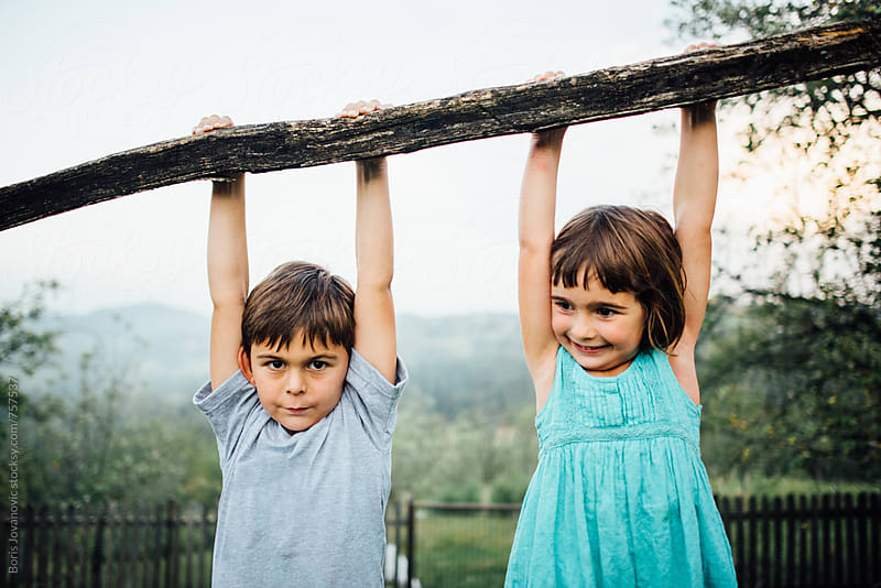 Brother and sister holding a branch and hanging from it by Boris Jovanovic for Stocksy United