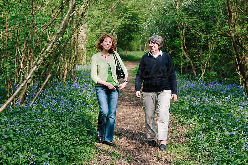 Senior mother and grown daughter walking in wood by Paul Phillips for Stocksy United