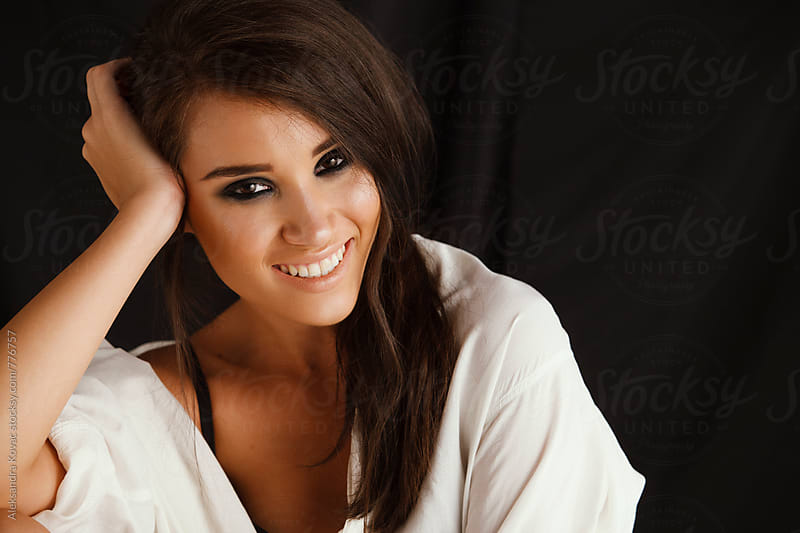 Studio portrait of a beautiful brunette woman smiling by Aleksandra Kovac for Stocksy United
