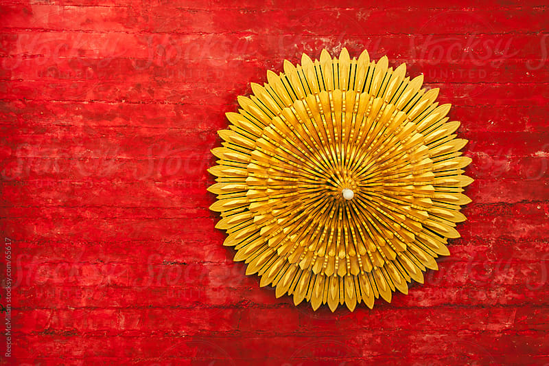 Elaborate yellow light on weathered red ceiling by Reece McMillan for Stocksy United