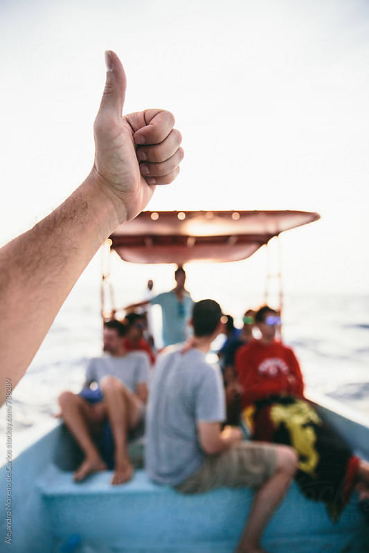 Male hand giving a thumbs up on a boat trip with a group of travelers in the sea by Alejandro Moreno de Carlos for Stocksy United