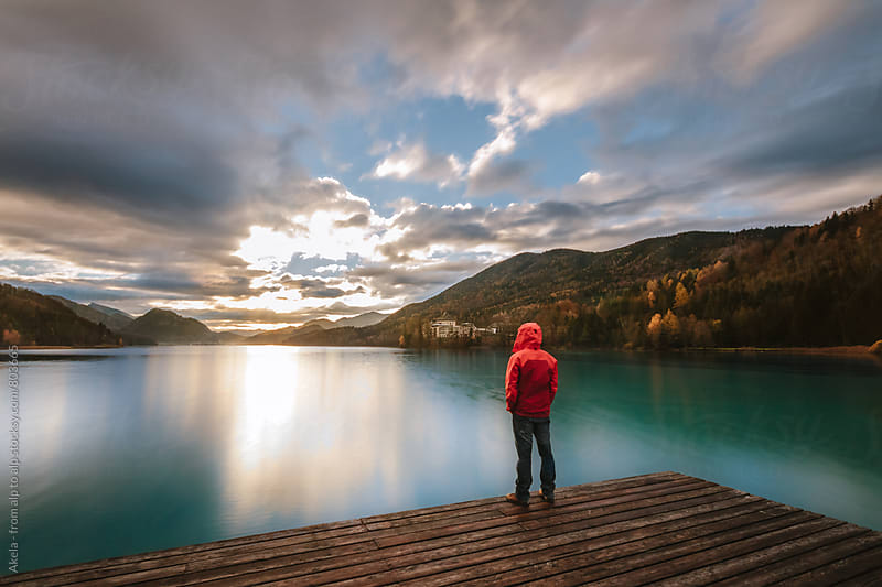 young man in red jacket standing on a jetty  at a lake enjoying the sunrise by Leander Nardin for Stocksy United