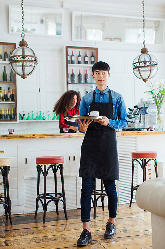 Young asian man wearing an apron holding a tray with coffee in a beautiful coffee shop. by BONNINSTUDIO for Stocksy United