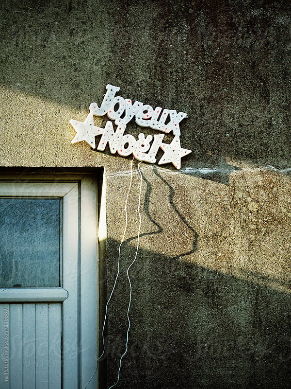 Joyeux Noel Light on a grunge wall by Ina Peters for Stocksy United