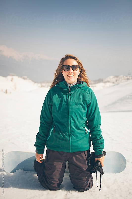 Happy female snowboarder on a ski slope smiling. by Koen Meershoek for Stocksy United