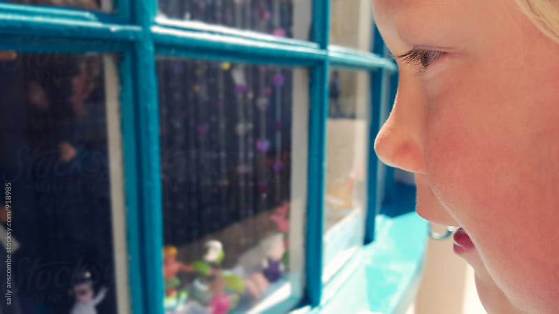 Child looking at toys through a shop window by sally anscombe for Stocksy United