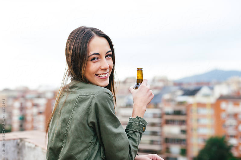Smiling young woman holding a bottle of beer on a rooftop. by BONNINSTUDIO for Stocksy United