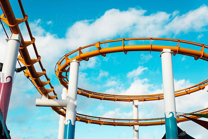 Tracks of orange roller coaster against blue sky by Alejandro Moreno de Carlos for Stocksy United