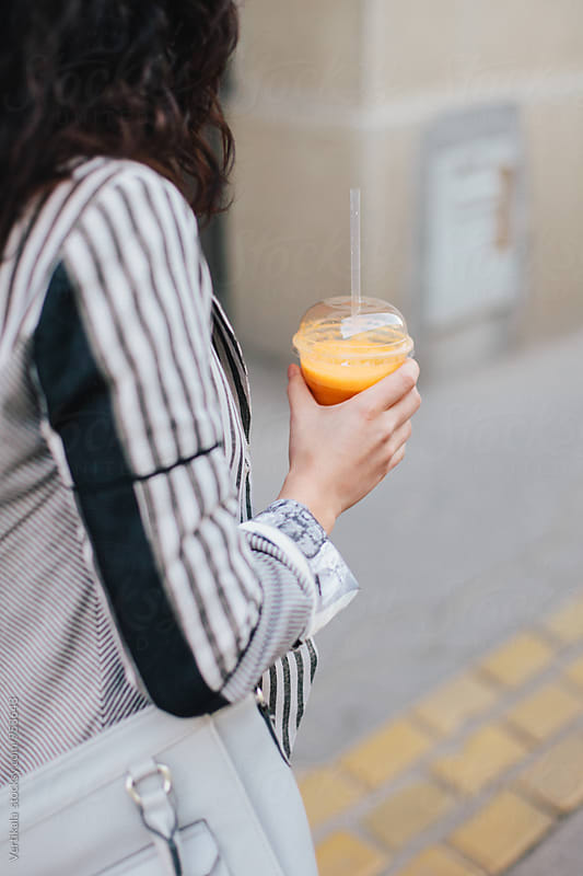 Woman drinking a smoothie in the street by VeaVea for Stocksy United
