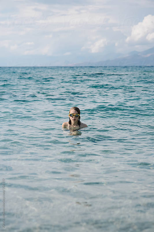 Lone girl in the sea.  by Kirstin Mckee for Stocksy United