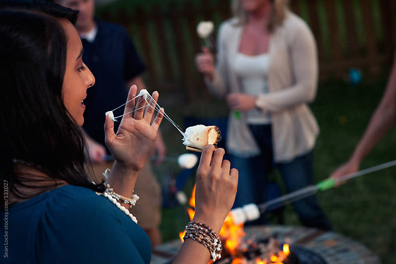 Party: Woman Eats Messy S'more By Fire by Sean Locke for Stocksy United