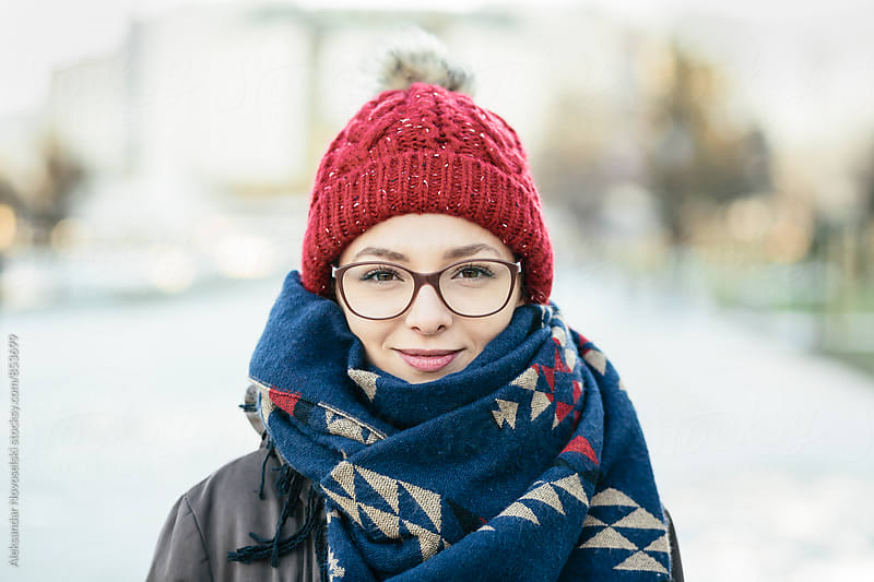 Beautiful young woman with glasses , smiling in urban environment by Aleksandar Novoselski for Stocksy United