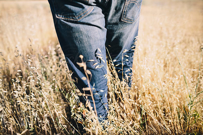Closeup of man wearing jeans walking in field by Lior + Lone for Stocksy United