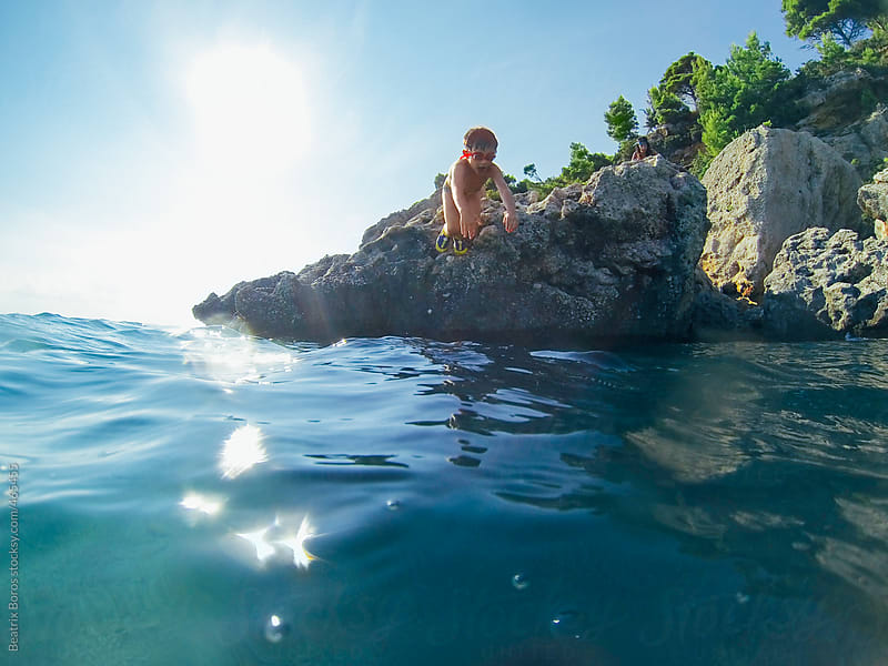 Boy jumping into the water from a rock on a sunny day  by Beatrix Boros for Stocksy United