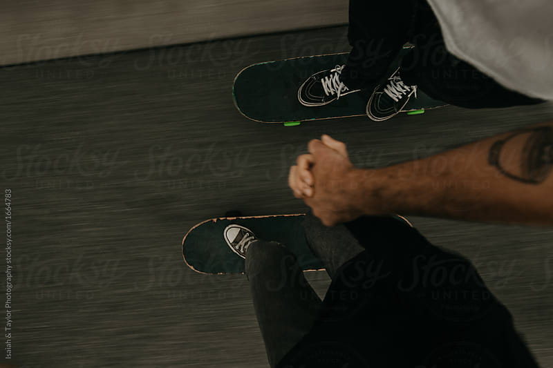 Skateboard Couple enjoying young love while holding hands skateboarding together