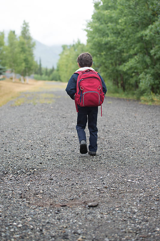 young boy walks the path to school wearing a backpack by Tara Romasanta for Stocksy United