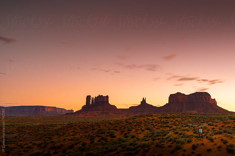 Backpacker Hiking at Monument Valley Utah USA Landscape At Dusk Under Colorful Red Tobacco Sky by JP Danko for Stocksy United