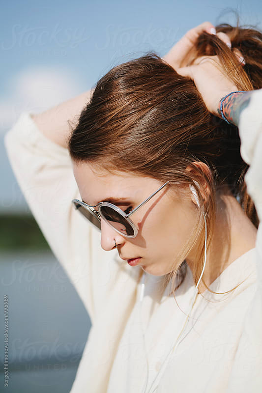 Portrait of a young tattooed woman in sunglasses by Sergey Filimonov for Stocksy United
