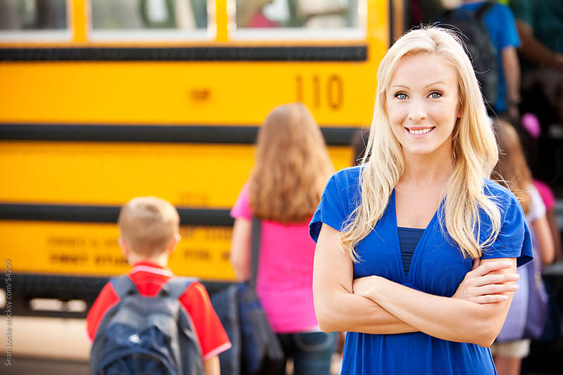 School Bus: Pretty, Cheerful Mother with Bus Behind by Sean Locke for Stocksy United