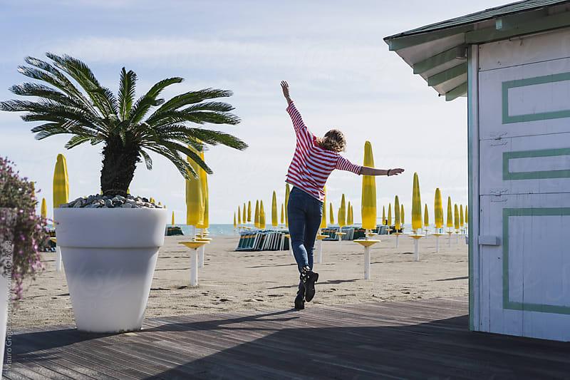 Woman enjoying a sunny day on the beach by Mauro Grigollo for Stocksy United