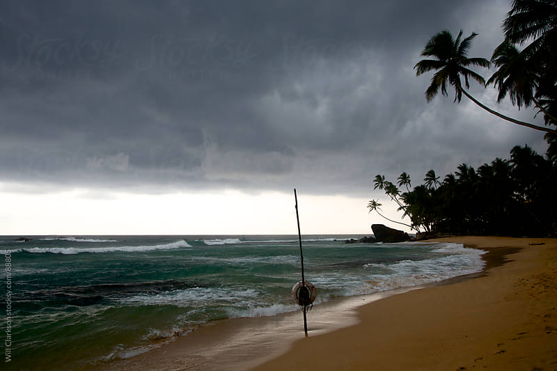 Palm beach with a storm overhead, stick fisherman stick in the foreground by Will Clarkson for Stocksy United