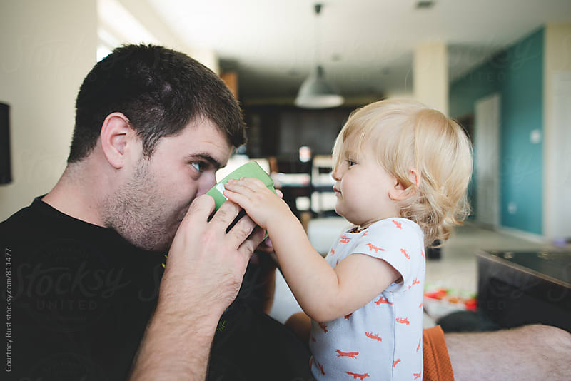 Helping Daddy drink  by Courtney Rust for Stocksy United