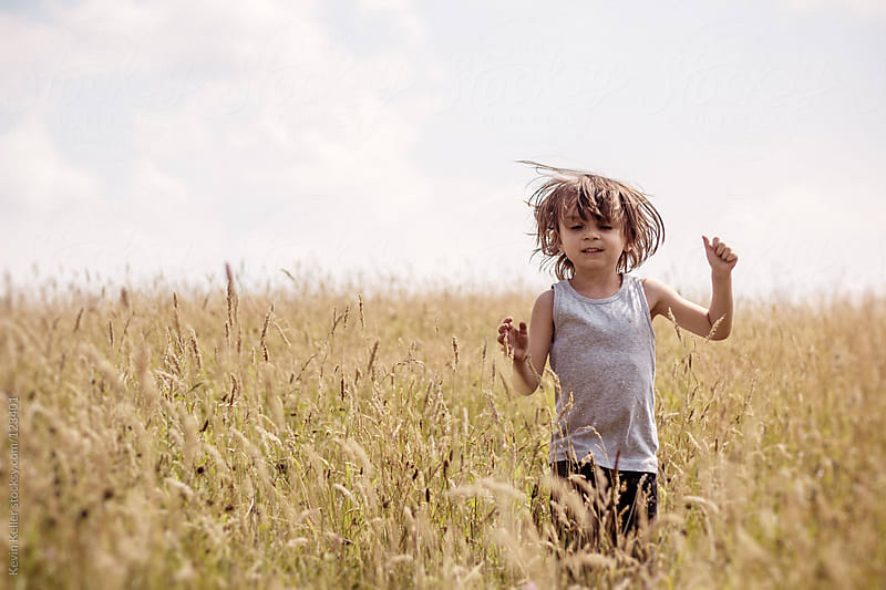Young Boy Jumping Through a Golden Field by Kevin Keller for Stocksy United