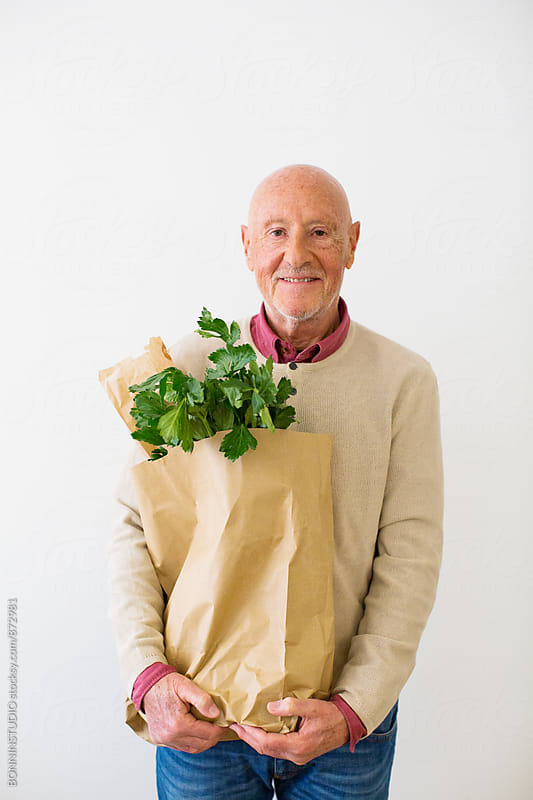 Portrait of an elderly man holding organic food on bag. by BONNINSTUDIO for Stocksy United