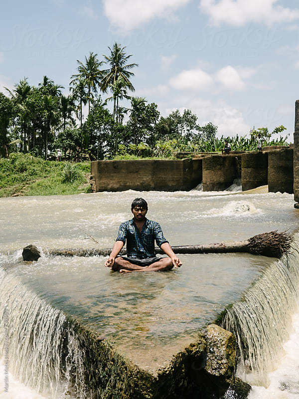 Indian man meditating in the river by Martin Matej for Stocksy United