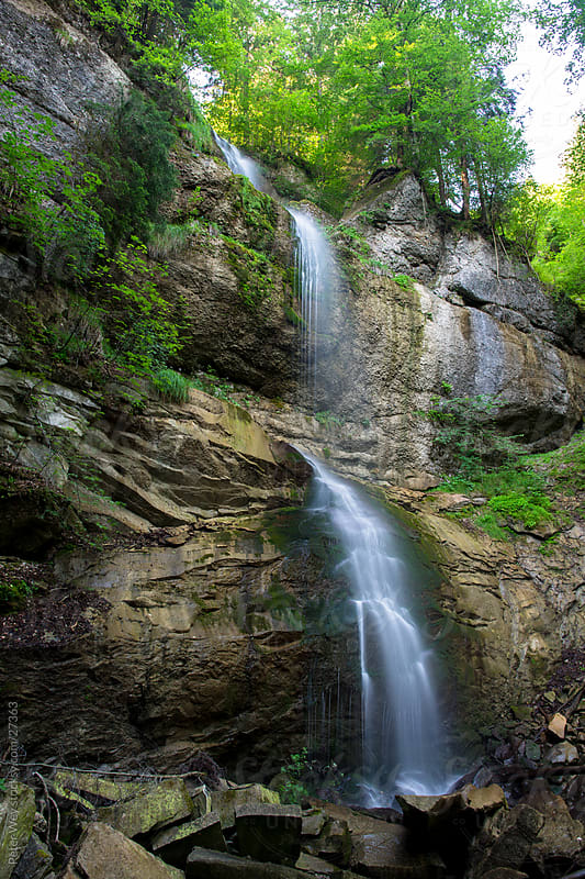Small waterfall inside green forest by Peter Wey for Stocksy United