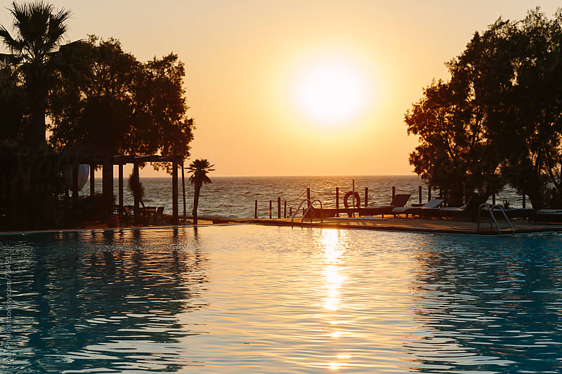 Sunset over pool and sea by Paul Phillips for Stocksy United