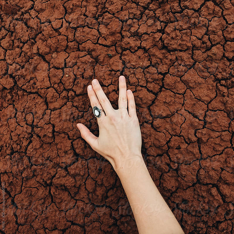 Hand on cracked, red clay in the painted hills by KATIE + JOE for Stocksy United