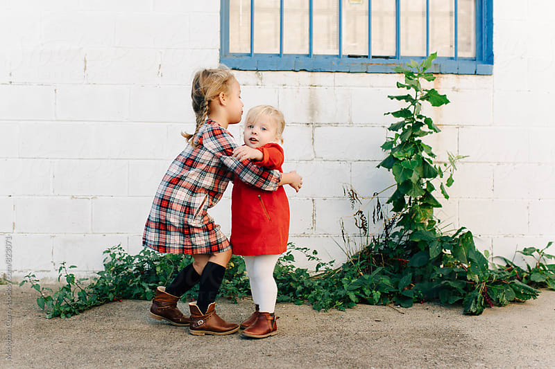 portraits of two young sisters dressed in holiday colors in the middle of a hug by Meaghan Curry for Stocksy United
