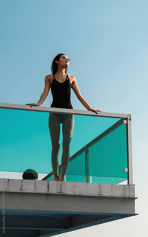 Attractive young female in black tricot standing on balcony and looking to sun. by Marko Milanovic for Stocksy United