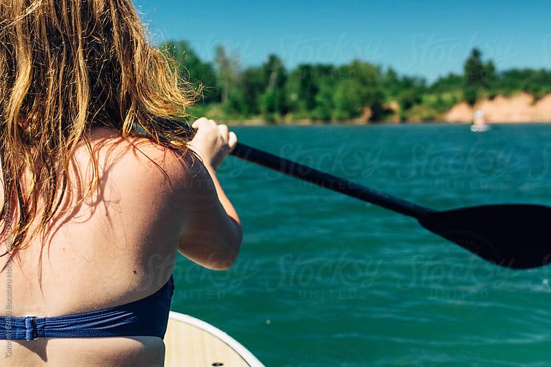 Teenage girl on a paddleboard by Gabriel (Gabi) Bucataru for Stocksy United