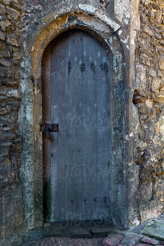 Old arched door inside a derelict church by Paul Phillips for Stocksy United
