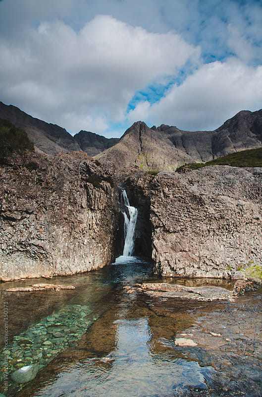 Small Waterfall with Mountains by Neil Warburton for Stocksy United