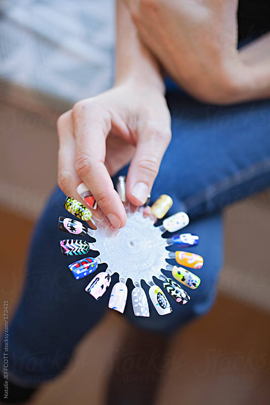 A lady's hand holding a nail art sample wheel waiting for her manicure by Natalie JEFFCOTT for Stocksy United