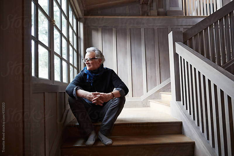 Portrait of stylish mature man with grey hair sitting on steps by Trinette Reed for Stocksy United
