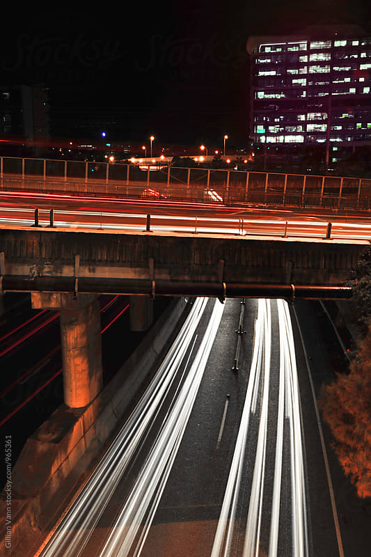 a bridge over a road with long headlight trails of moving traffic by Gillian Vann for Stocksy United