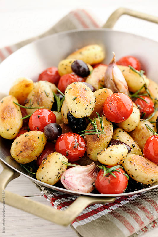 Rosemary Potatos with Cherry Tomatos, Calamata Olives and Garlic by Ina Peters for Stocksy United
