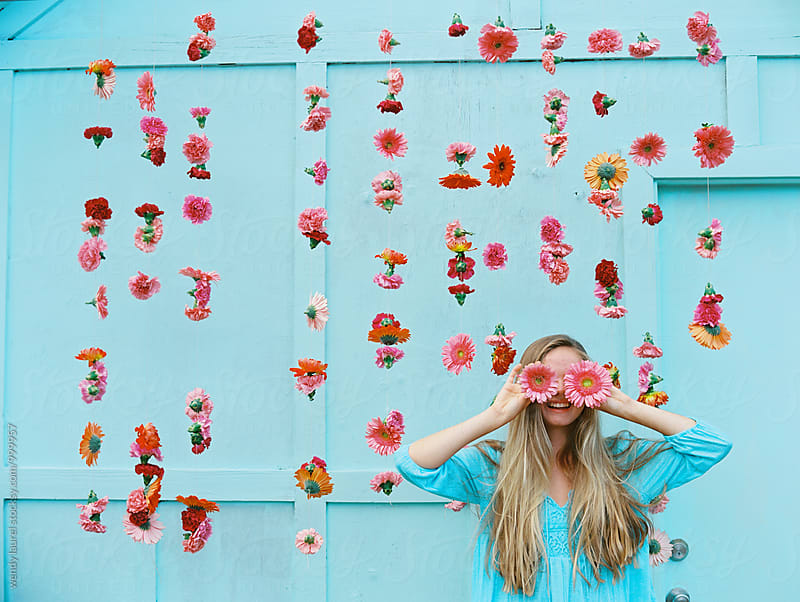 blonde girl with pink flowers over eyes against hanging pink florals by wendy laurel for Stocksy United