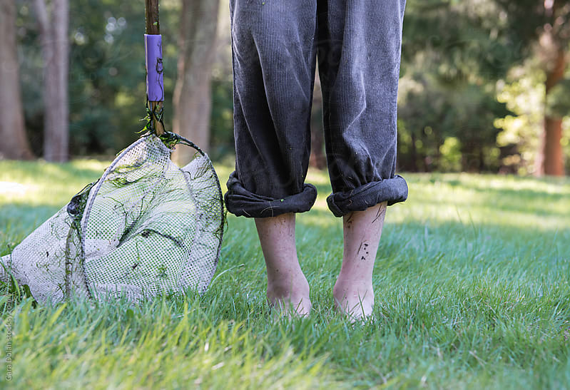 Muddy, wet child with rolled up pants and a net stands in the grass by Cara Slifka for Stocksy United