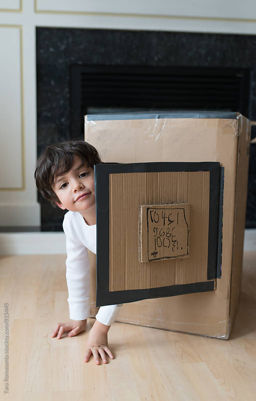 young child crawling out of a hand decorated cardboard box by Tara Romasanta for Stocksy United